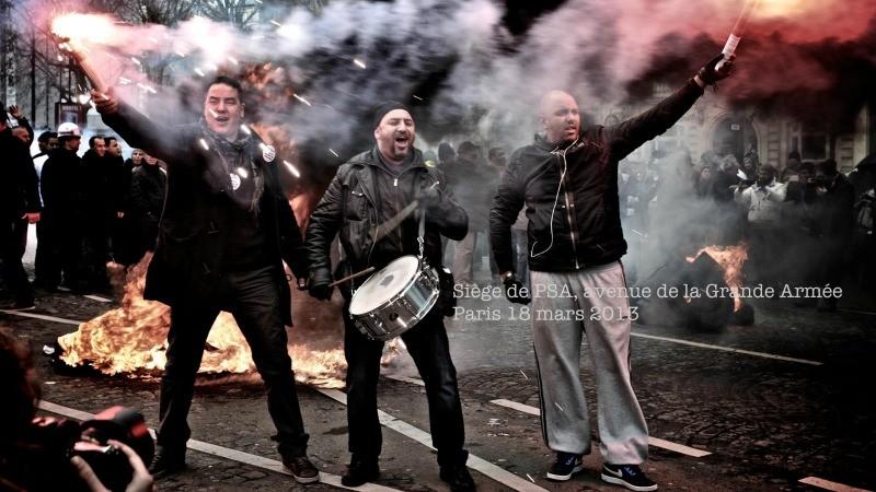 Le 18 mars 2013, des ouvriers de PSA manifestent devant le siège de leur entreprise. Main dans la main, unis par leur combat de classe.